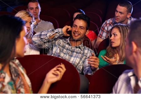 Confident young man talking on mobilephone in cinema, spectators looking angry.