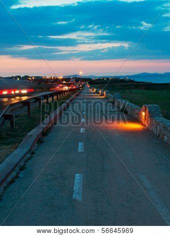 a dark cycling lane seen at sunset poster