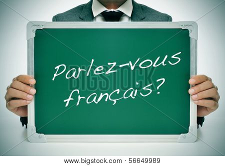 man wearing a suit holding a chalkboard with the question parlez-vous francais? do you speak french? written in it