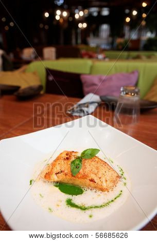 Braised fish fillet with broth sauce on plate