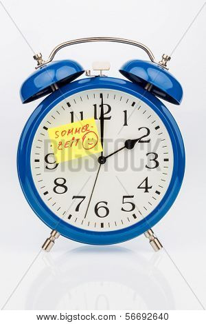 an alarm clock with a note as a reminder to the uhrumstellung at summer time