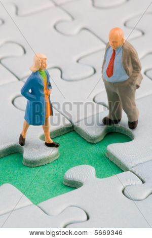 A couple standing in front of a missing jigsaw puzzle piece poster