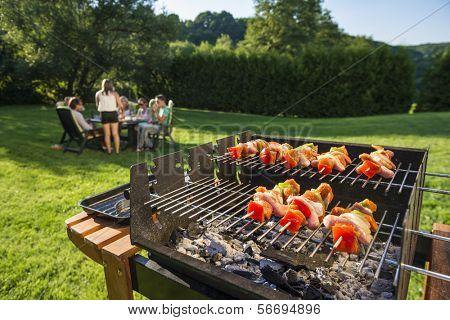 Shashlick Verlegung auf dem Grill mit einer Gruppe von Freunden im Hintergrund Essen und trinken in der l