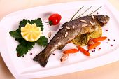 Fried trout with lemon and split almonds on white plate close up poster