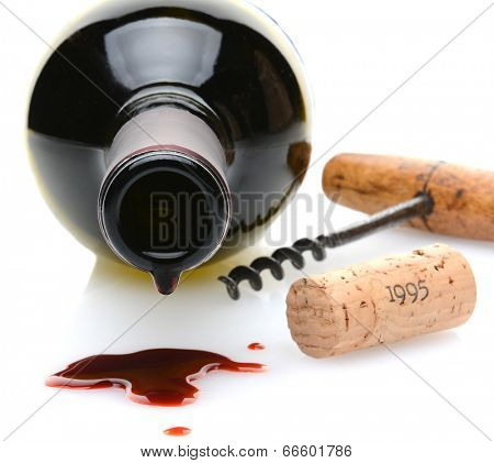 Closeup of a red wine bottle with a drip and wine spill in the foreground. A cork screw and cork to one side on a white background with slight reflection. Shallow depth of field with focus on the drip