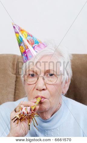 Senior mujer con sombrero de cumpleaños y generador de ruido