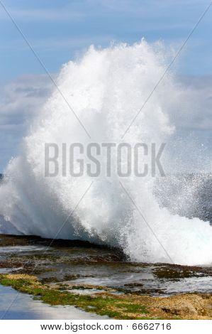 Wave crashing onto rock ledge.