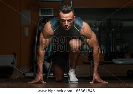 Strong Muscular Men Kneeling On The Floor - Almost Like Sprinter Starting Position poster