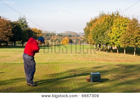 Male Golfer Teeing Off On A Par Three In Autumn