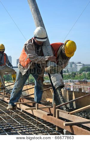 Two Construction Workers Using Hose from Concrete Pump
