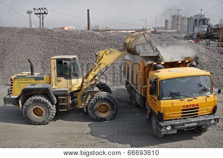 Yellow  Excavator Loads Gravel Into Orange Dumper Truck Tipper.