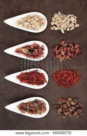 Frankincense, myrrh, sandalwood and fragrant rose flower petals over handmade lokta paper background.