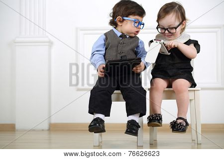 Two little kids in glasses sitting on white chairs: boy with tablet computer, girl with mobile phone