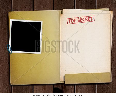 folder with TOP SECRET stamped across the front page and a blank photograph poster