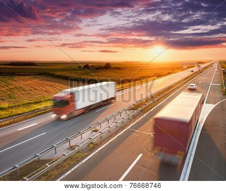 Two Red Trucks On Highway At Sunset