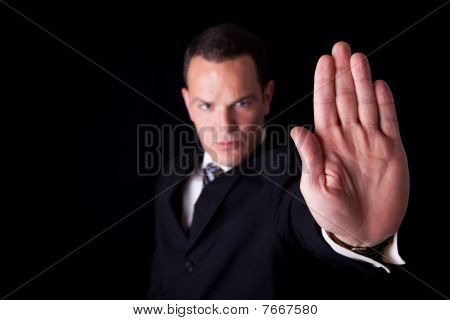 Businessman With His Hand Raised In Signal To Stop, Isolated On Black Background, Studio Shot
