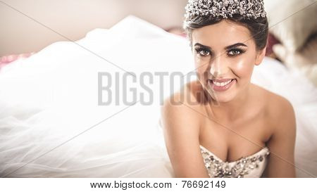 Gorgeous bride portrait in her wedding dress wearing tiara. Beautiful bridal makeup and hairstyle an