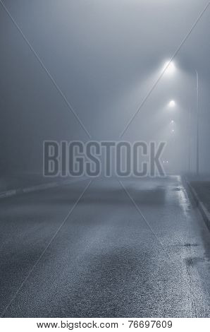 Street lights foggy misty night lamp post lanterns deserted road in mist fog wet asphalt tarmac car headlights approaching blue key, vertical poster