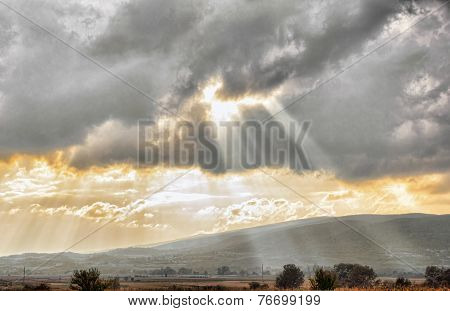 Golden Sunset Through Clouds Over Dramatic Sky In Landscape Concept