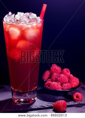 Red raspberry drink  with ice cube and plate of berry on black background. Cocktail card 18