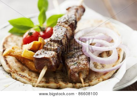 grilled meat skewer on pita bread