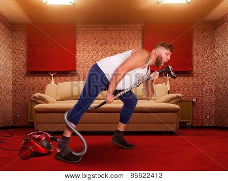 Adult man sings to the vacuum cleaner at home interior