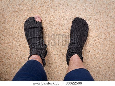 Male feet in old leaky socks