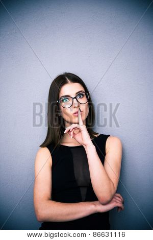 Portrait of a beautiful woman in glasses with finger over lips. Making shhh sign. Be quiet!!! Standing over gray background. Wearing black fashion dress. Looking at the camera.