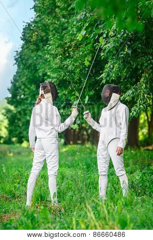 Two fencers women staying in park with crossed rapiers getting ready for competition