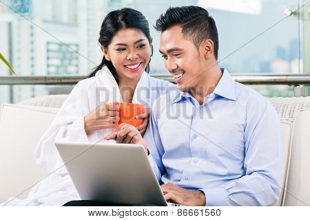 Businessman working in home office as telecommuter, his wife is bringing coffee