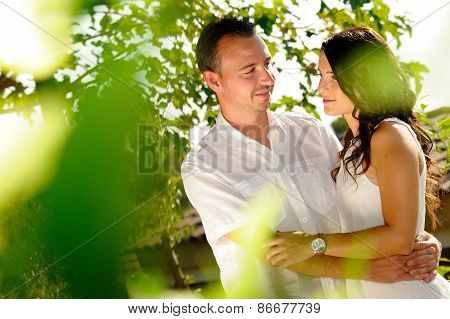 Young Couple Looking Accomplices Among Trees