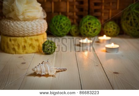 Sea shell on foreground, sponges, candles and rattan balls behind