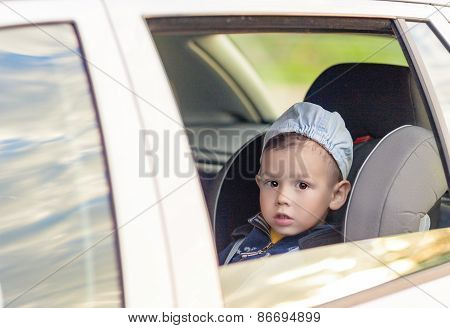 Safety Concept: Portrait Of Young Caucasian Happy Little Boy Sitting On A Car Safety Seat Chair