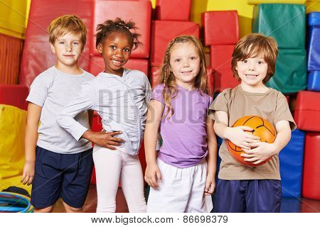 Children forming team for ball game in gym of a kindergarten