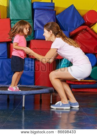 Girl jumping on trampoline with nursery teacher during children sports