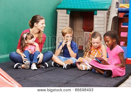 Group of children with nursery teacher reading a book in preschool