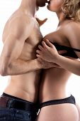 Unrecognizable young half naked couple love play guy in jeans undressing girl taking off her black bra studio shot white background close-up poster