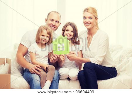 family, children, accomodation and home concept - smiling parents and two little girls holding green house