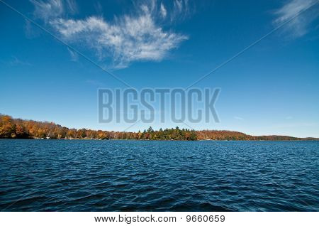 Canadian Lake With Autumn Colours And Blue Sky
