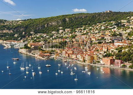 Coast aerial view of scenic French Riviera town Villefranche-sur-Mer with leisure boats anchored in harbor, citadel and fort Mont Alban on hill.