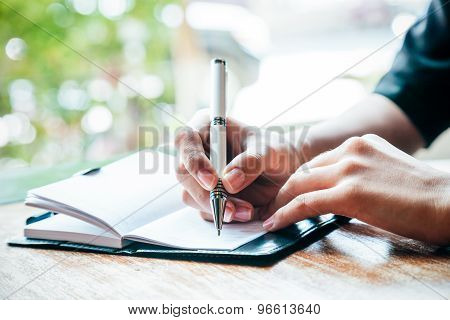 close up of woman writing her journal poster