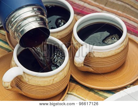 Three Ceramic Cups And Thermos With Coffee