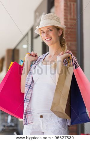 Woman holding shopping bags and wearing a trilby hat