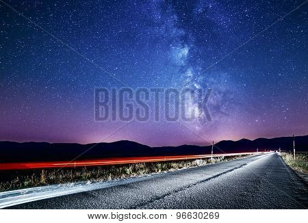 Night sky with milky way and stars. Night road illuminated by car. Light trails poster