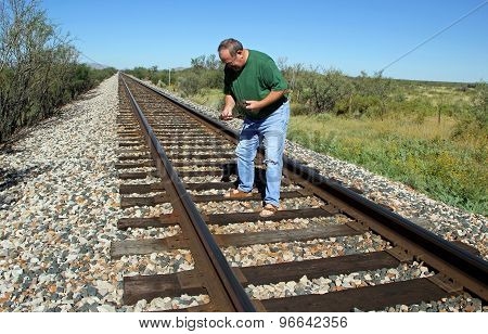 Man on Railroad Tracks Searching for Rusted Cut Spikes