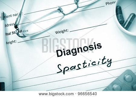 Diagnosis Spasticity and tablets on a wooden table.