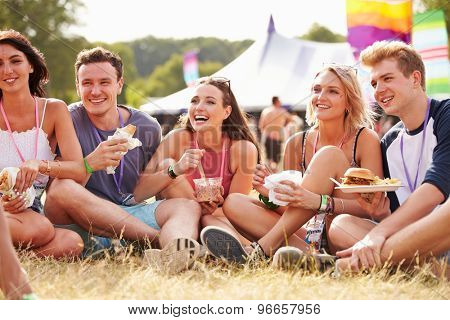 Friends sitting on the grass eating at a music festival poster