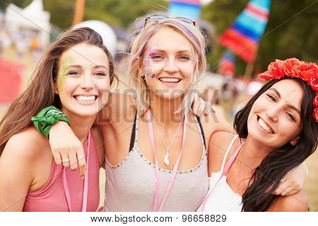 Girl friends with arms around each other at a music festival