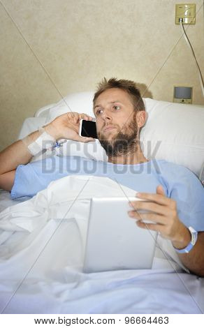 Business Man In Hospital Room Lying In Bed Sick And Injured Working With Mobile Phone And Digital Pa