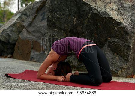 young fitness woman practicing yoga Pigeon Pose Kapotasana near rocks